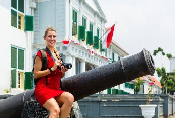Woman tourist sitting on cannon in old Batavia colonial district of Jakarta, Indonesia