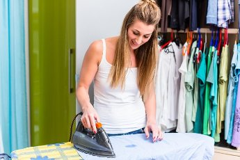 Happy young woman in front of wardrobe ironing the laundry