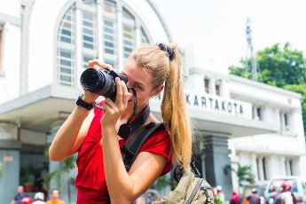 Woman photographing train station sightseeing with camera in Jakarta, Indonesia