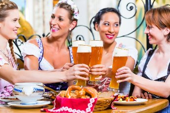 Girls toasting with wheat beer in Bavarian pub in front of pretzel