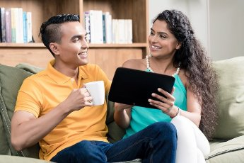 Happy young couple enjoying while watching videos on digital tablet