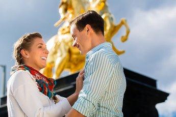 Tourist couple in Dresden in front of Goldener Reiter statue
