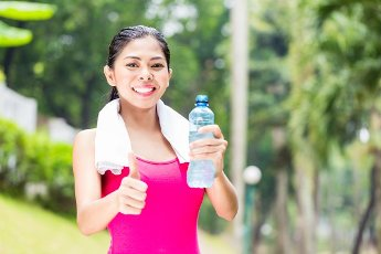 Asian woman having successful sport training giving thumbs up with water bottle in her hands