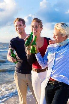 Friends enjoying bottled beer at sunset on German north sea beach