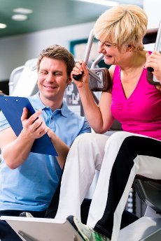 Trainer in sport gym assisting senior woman exercising on resistance machine, showing her the training schedule