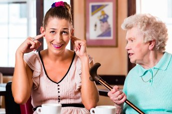 Grandmother and granddaughter having argument in cafe, the young woman is closing her ears