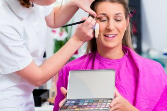 Woman with beautician in cosmetic salon receiving makeup