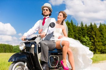 Wedding concept, bride and groom on motor scooter, she is showing her garter on leg