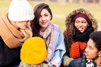 Multi-ethnic group of young people having a good time together outdoors in a cold day