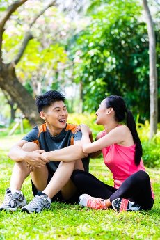 Asian Chinese man and woman sitting on lawn after fitness sport training in park