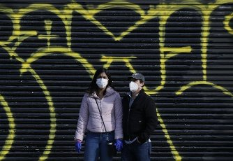 Pedestrians wear protective face masks standing on the sidewalk of the West Side Highway near where the USNS Comfort Navy ship is docked at Pier 90 on the Hudson River in New York City on Wednesday, April 1, 2020. The floating hospital in the form of a Navy ship will arrive in New York City on Monday to relieve pressure on hospitals already overwhelmed with coronavirus patients. The USNS Comfort is set to dock around 10 a.m. and it will be ready to take in patients within 24 hours. Photo by John Angelillo/