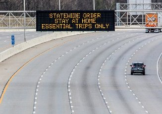 Sparse traffic passes a sign of the times on Interstate 465 on Wednesday, April 1, 2020, in Indianapolis, Indiana. Indiana Gov. Eric Holcomb issued a stay-at-home order for all Hoosiers due the rapid spread of the coronavirus on March 23. Photo by Edwin Locke/