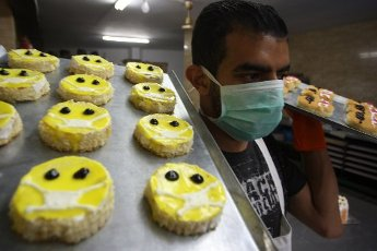 Palestinians make cakes shaped like a character wearing a mask amid concerns about the spread of coronavirus disease (COVID-19), in a bakery in Rafah in the southern Gaza Strip on Friday, April 3, 2020. Photo by Ismael Mohamad/