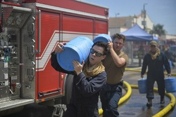 U.S. Navy Sailors carry barrels of aqueous film-forming foam (AFFF) in support of putting out a fire onboard USS Bonhomme Richard (LHD 6) at Naval Base San Diego on July 12, 2020. On the morning of July 12, a fire was called away aboard the ship while it was moored pier side at Naval Base San Diego. Base and shipboard firefighters responded to the fire. USS Bonhomme Richard is going through a maintenance availability, which began in 2018. Photo by MC2 Austin Haist\/U.S. Navy