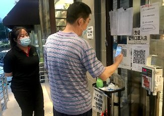 A Chinese man registers his contact information before being allowed to enter a food market in Beijing on Thursday, July 16, 2020. The emergence of a coronavirus cluster in the capital last month has led to increased scrutiny of major food markets that sell both imported and domestic food. Photo by Stephen Shaver