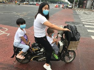 A mom waits at a traffic light with her kids, all wearing protective face masks, in Beijing on Thursday, July 16, 2020. China reported just one new confirmed case of the Covid-19 in the past 24 hours and two asymptomatic cases, as the U.S. struggles to fight the rising infections and deaths across the country. Photo by Stephen Shaver