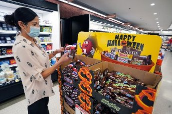Schnucks Markets co-manager Alea Doyen puts bags of candy in order as the first wave of Holloween candy appears in stores in Ladue, Missouri on Wednesday, August 12,2020. Sources have said the date of Holloween may change due to the Pandemic. Photo by Bill Greenblatt