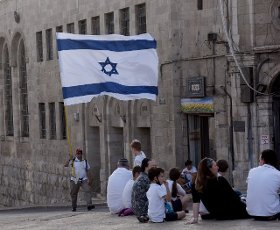 An Israeli carries a large national flag during the annual Jerusalem Day march marking the reunification of Jerusalem during the Six Day War on Monday, May 10, 2021. The march was cut short when Hamas fired rockets towards Jerusalem. Photo by Debbie Hill