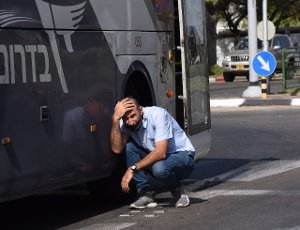 An Israeli takes cover as a siren sounds alerting of incoming rockets fired from the Gaza Strip in Ashkelon in southern Israel, on Tuesday, May 11, 2021. Photo by Debbie Hill