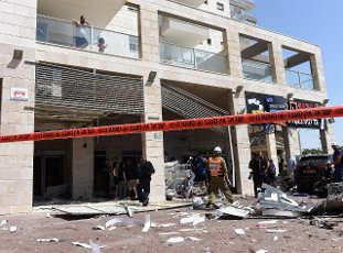 Israelis look at an apartment building hit by a rocket fired from the Gaza Strip in Ashkelon in southern Israel, on Tuesday, May 11, 2021. Photo by Debbie Hill