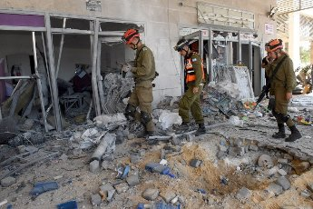 Israeli soldiers look at the damage of a building hit by a rocket fired from the Gaza Strip in Ashkelon in southern Israel, on Tuesday, May 11, 2021. Photo by Debbie Hill