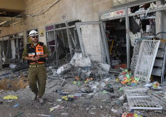 An Israeli soldier looks at the damage in a building hit by a rocket fired from the Gaza Strip in Ashkelon in southern Israel, on Tuesday, May 11, 2021. Photo by Debbie Hill
