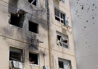 An Israeli woman stands in a window in an apartment building hit by a rocket fired from the Gaza Strip in Ashkelon in southern Israel, on Tuesday, May 11, 2021. Photo by Debbie Hill