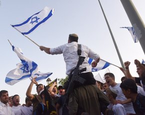 An Israeli with an automatic weapon holds the national flag during the annual Jerusalem Day march marking the reunification of Jerusalem during the Six Day War on Monday, May 10, 2021, in Jerusalem. The march was cut short when Hamas fired rockets towards Jerusalem. Photo by Debbie Hill
