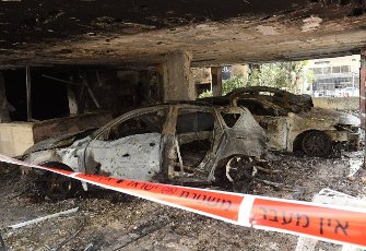 Police tape marks off burnt cars parked under an apartment building damaged by a rocket fired from the Gaza Strip in Petah Tikva, near Ben Gurion International Airport, on Thursday, May 13, 2021. Major European and U.S. airlines have cancelled flights to Israel in light of the deteriorating security situation. Photo by Debbie Hill