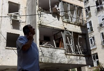 An Israeli man inspects the damage outside an apartment building hit by a rocket fired from the Gaza Strip in Petah Tikva, near Ben Gurion International Airport, on Thursday, May 13, 2021. Major European and U.S. airlines have cancelled flights to Israel in light of the deteriorating security situation. Photo by Debbie Hill