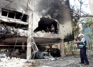 An Israeli man inspects the damage at an apartment building hit by a rocket fired from the Gaza Strip in Petah Tikva, near Ben Gurion International Airport, on Thursday, May 13, 2021. Major European and U.S. airlines have cancelled flights to Israel in light of the deteriorating security situation. Photo by Debbie Hill