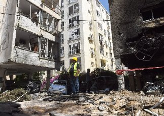 An Israeli man inspects the damage outside apartment buildings hit by a rocket fired from the Gaza Strip in Petah Tikva, near Ben Gurion International Airport, on Thursday, May 13, 2021. Major European and U.S. airlines have cancelled flights to Israel in light of the deteriorating security situation. Photo by Debbie Hill