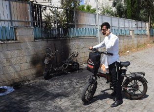 An Israeli stops by a scooter burnt from shrapnel from a rocket fired from the Gaza Strip in Petah Tikva, near Ben Gurion International Airport, on Thursday, May 13, 2021. Major European and U.S. airlines have cancelled flights to Israel in light of the deteriorating security situation. Photo by Debbie Hill