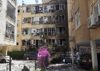 An Israeli man looks at the damage in an apartment building hit by a rocket fired from the Gaza Strip in Petah Tikva, near Ben Gurion International Airport, on Thursday, May 13, 2021. Major European and U.S. airlines have cancelled flights to Israel in light of the deteriorating security situation. Photo by Debbie Hill