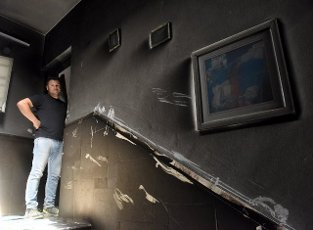 An Israeli looks at the damage in an apartment building hit by a rocket fired from the Gaza Strip in Petah Tikva, near Ben Gurion International Airport, on Thursday, May 13, 2021. Major European and U.S. airlines have cancelled flights to Israel in light of the deteriorating security situation. Photo by Debbie Hill