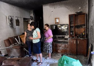 Members of the Sror family inspect the damage in their apartment, in a building hit by a rocket fired from the Gaza Strip in Petah Tikva, near Ben Gurion International Airport, on Thursday, May 13, 2021. Major European and U.S. airlines have cancelled flights to Israel in light of the deteriorating security situation. Photo by Debbie Hill