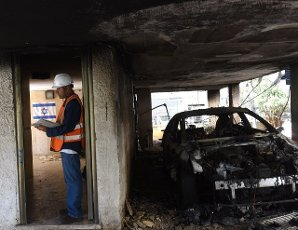 An Israeli inspects the damage in an apartment building hit by a rocket fired from the Gaza Strip in Petah Tikva, near Ben Gurion International Airport, on Thursday, May 13, 2021. Major European and U.S. airlines have cancelled flights to Israel in light of the deteriorating security situation. Photo by Debbie Hill