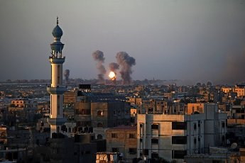 Smoke and a ball of fire rise above buildings in Khan Yunis in the southern Gaza Strip, during an Israeli air strike, on Wednesday on May 12, 2021. - Israeli air raids in the Gaza Strip have hit the homes of members of the Hamas militant group, the military said Wednesday, with the territory\'s police headquarters also targeted. Photo by Ismael Mohamad