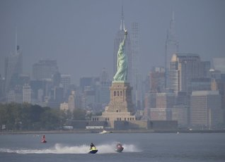 People ride jet skis in the Hudson River with a view of the Statue of Liberty in Bayonne, New Jersey on Wednesday, June 9, 2021. Photo by John Angelillo