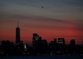 The sky fills with colors behind One World Trade Center, the Statue of Liberty and the Manhattan skyline before sunrise from Bayonne, New Jersey on Thursday, June 10, 2021. Photo by John Angelillo