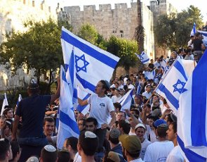 Right-wing Israelis carry the national flag and shout at Palestinians and the press during the controversial Flag Parade outside the Damascus Gate in Jerusalem\'s Old City on Tuesday, June 15, 2021. Photo by Debbie Hill