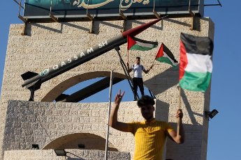A Palestinian holds the national flag next to a Hamas rocket memorial, during a protest against an Israeli ultra nationalist March of the Flags in Jerusalem\'s Old City in Rafah in Southern Gaza on Tuesday, June 15, 2021, The Israeli march celebrates the anniversary of Israel\'s 1967 occupation of Jerusalem\'s eastern sector. Photo by Ismael Mohamad