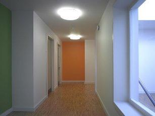 Corridor with orange coloured wall. Watford Music Centre, Watford, United Kingdom. Architect: Tim Ronalds Architects, 2008