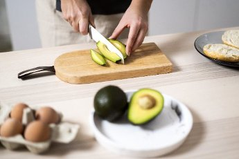 Hands of woman cutting avocado on cutting board