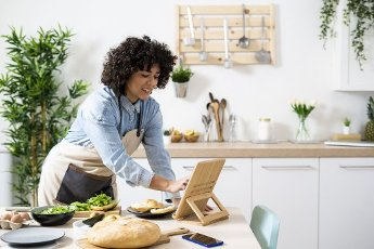 Young woman using digital tablet while preparing vegan sandwiches in kitchen