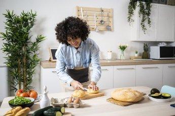 Young woman preparing vegan sandwiches in kitchen