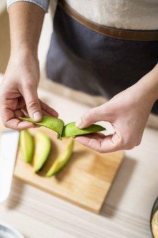 Hands of woman peeling avocados