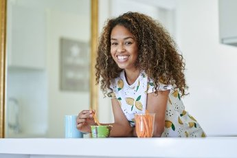 Smiling woman with guacamole sauce and carrots leaning on kitchen counter at home