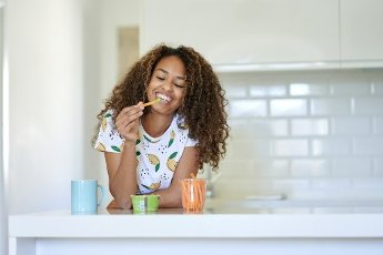Smiling young woman having guacamole with carrots in kitchen