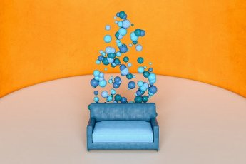 Blue sofa and spheres against orange wall
